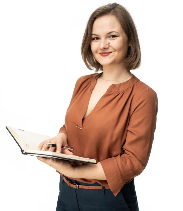 Uśmiechnięta kobieta w średniej długości brązowych włosach, ubrana w jasno brązową koszulę i ciemno granatowe spodnie z paskiem tego samego koloru co koszula. Stoi bokiem i w prawej ręce trzyma otwarty notes, a w lewa ręka położona jest na notesie i jest w niej trzymany długopis